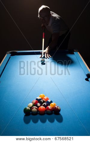 Man playing a game of pool lining up as the break shooter as he takes aim with his cue and ball at the triangular formation of object balls in a dark shadowy pub or bar