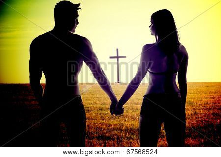 Atmospheric conceptual image of the silhouettes of a romantic young couple holding hands standing with their backs to the camera in a field with a cross visible beyond them