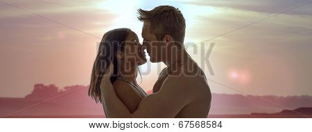 Young couple standing in profile enjoying an intimate romantic sunset kiss against a delicate pink desert landscape