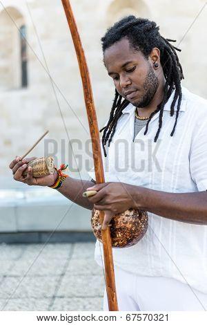 African Capoeira Rastamanplaying a instrument berimbau
