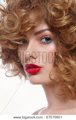 Portrait of young beautiful blue-eyed woman with curly hair and red lipstick
