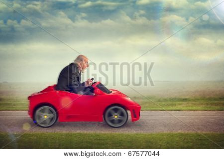 Senior Man Driving A Toy Racing Car