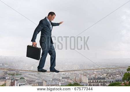 Businessman Walking Tightrope Above City