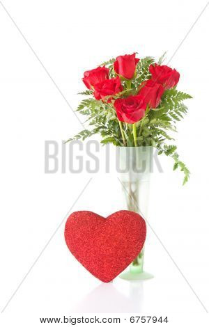vase arrangement of red roses with a red heart decoration