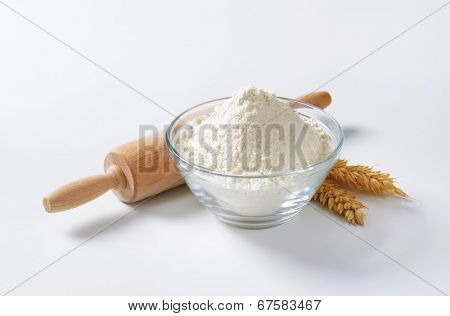 glass bowl of soft wheat flour, with wooden rolling pin and wheat ear