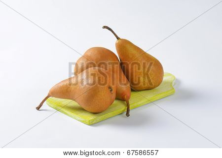 three pears on the wooden cutting board