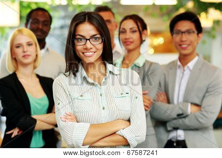 Smiling businesswoman with arms folded standing in front her colleagues