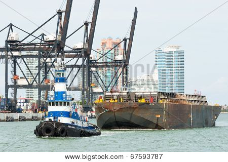 MIAMI,USA - MAY 27,2014 : Tugboat pulling a barge in the Port of Miami with containers and cranes on the background