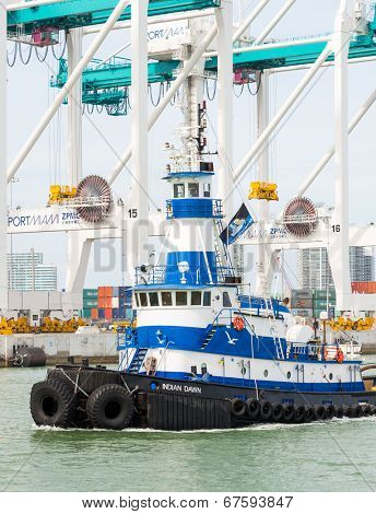 MIAMI,USA - MAY 27,2014 : Tugboat sailing in the Port of Miami with containers and cranes on the background