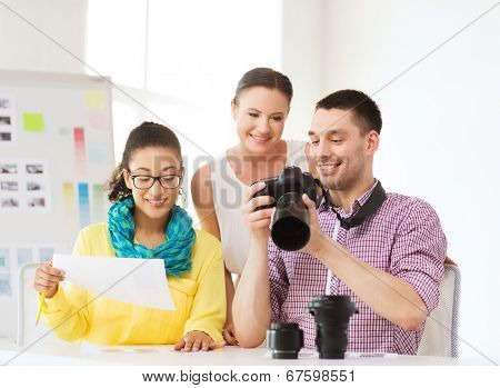 business, education, office and startup concept - smiling creative team with photocamera working in office