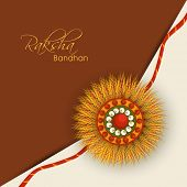 stock photo of rakshabandhan  - Beautiful rakhi design on brown and beige background on the occasion of Happy Raksha Bandhan - JPG
