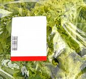 image of iceberg lettuce  - iceberg lettuce in plastic bag package with price tag - JPG