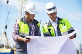 foto of blueprints  - Two engineers at construction site are inspecting works on site according to design drawings - JPG