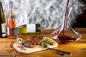 stock photo of graphene  - A big pork steak with spices tomatoes and bottles of wine on the background