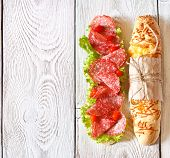 stock photo of sweetie  - Salami sandwich with lettuce and sweety drop peppers on a white wooden board with place for text - JPG
