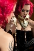 picture of bustiers  - Sexy young woman holding carnival mask in front of mirror - JPG