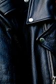stock photo of lapel  - High contrast close up of black leather biker jacket showing zipper shoulder and snap collar and lapel in sunshine - JPG