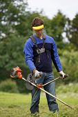 pic of trimmers  - Man working with grass trimmer in summer - JPG