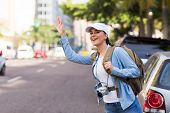 foto of hail  - happy young female tourist hailing for a cab in the city - JPG