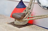 image of bollard  - Old mooring bollard and boat in port Croatia - JPG