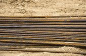 stock photo of reinforcing  - Reinforcing steel bars armature for building armature on sand in work place