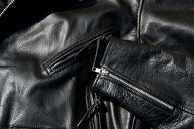 picture of zipper  - High contrast close up of black leather motorcycle jacket showing zippered pockets and portion of sleeve in sunshine - JPG