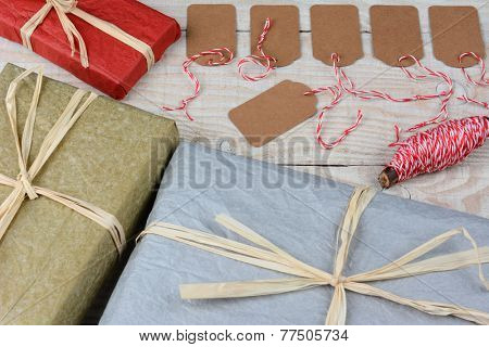 Overhead shot of a group of blank gift tags surrounded by wrapped Christmas presents on a white rustic table. Horizontal format with focus on the gift tags.