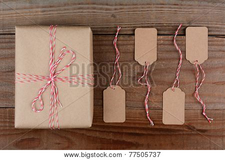 Overhead shot of a Christmas Package wrapped in plain brown paper and tie with red and white string. Four blank tags are next to the gift on a dark rustic wood table.