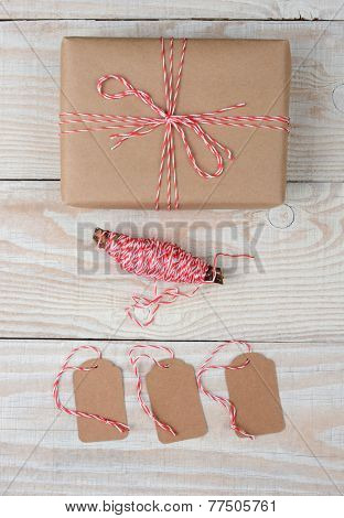 High angle shot of a Christmas Package wrapped in plain brown paper and tied with red and white string. Three blank tags and spool of string are below the gift on a white rustic table.