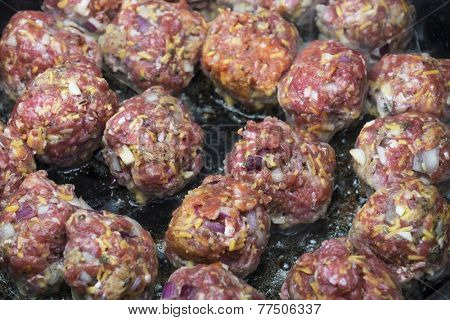 Italian style meatballs cooking on a pan