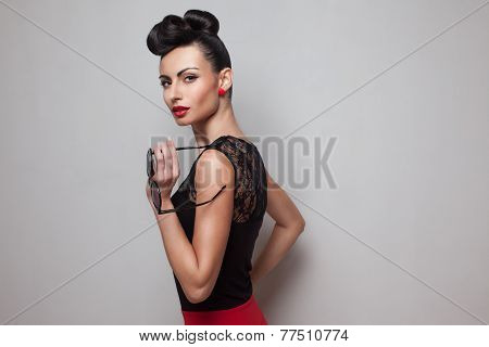 Pin Up Style Woman Holding Round Sunglasses Posing In Red Skirt. Red Lips. Updo, Twisted High Bun. T