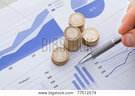 Pen With Line And Coins Graphs On Desk