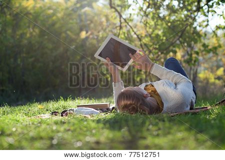 Woman Lying On Bedding On Green Grass With Ipad During Picknic In The Park