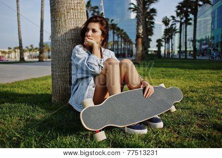 Charming hipster girl sitting on the grass at sunset holding her longboard