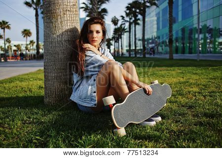 Attractive young hipster girl sitting on the grass looking away