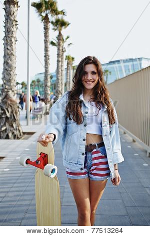 Attractive hipster girl holding her longboard standing on road