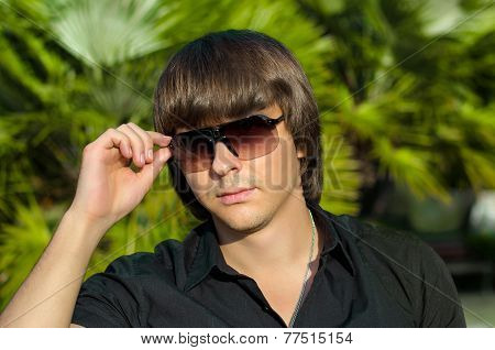 Trendy Handsome Man Wearing In Sunglasses Over Palm, Outdoor Portrait.