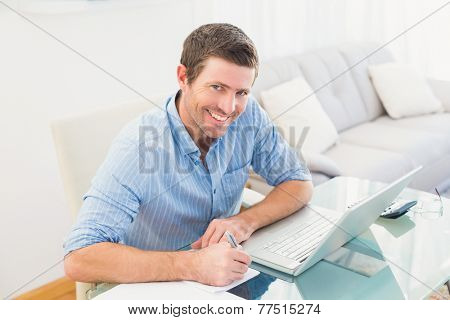 Smiling businessman writing at his desk at his office