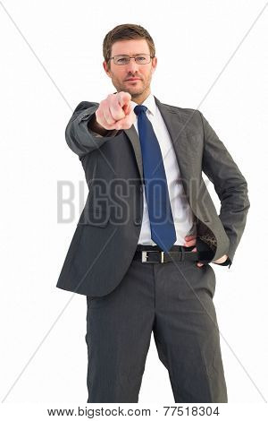 Frowning businessman pointing at camera on white background