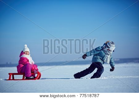 Little boy pulling sledge with his sister on