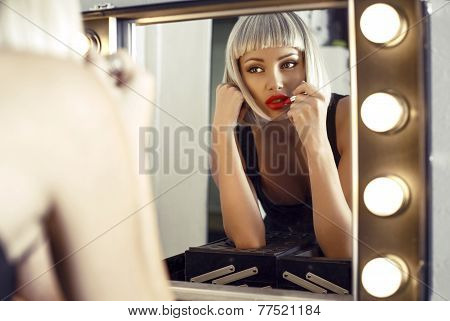 Sensual Woman In Blond Wig Doing Makeup In Dressing Room