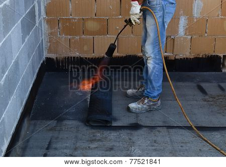 Worker preparing part of bitumen roofing