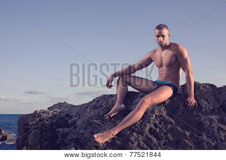 very muscular handsome guy sitting on rocky beach, on sky background. outdoor