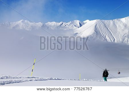 Snowboarder On Off-piste Slope And Mountains In Mist