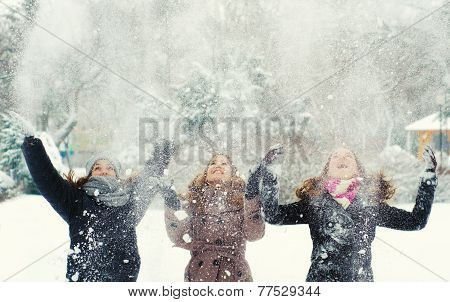 Three Teenage Girls Throwing Snow
