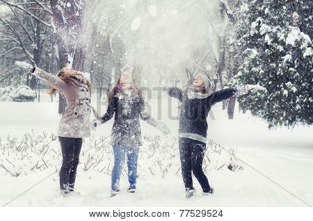 Happy Teenage Girls Throwing Snow In The Air