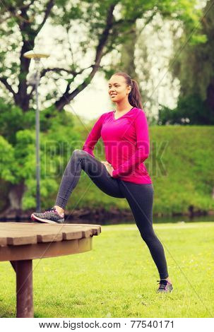 fitness, sport, training, park and lifestyle concept - smiling african american woman stretching leg on bench outdoors