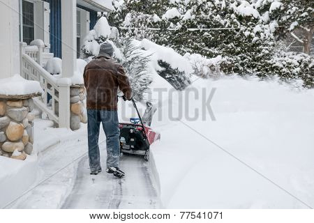 Man using snowblower to clear deep snow on driveway near residential house after heavy snowfall