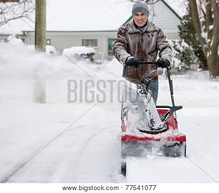 Man clearing deep snow from residential driveway after heavy snowfall. Focus on snowblower.