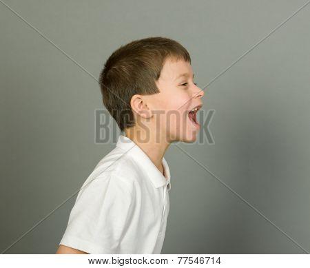 grimacing boy portrait on grey background